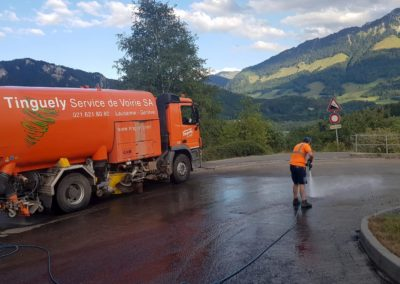 Camion de balayage Tinguely sur route de montagne en Suisse
