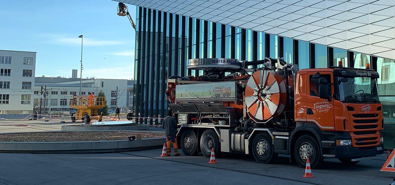 camion de curage Tinguely devant chantier vue de profil
